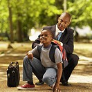 Front view of father closing son´s schoolbag (10-11)