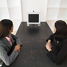 Elevated view of two businesswomen having video conference