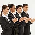 Side view of four business executives standing in a line and applauding