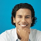 Front view portrait of young man smiling with hand touching chin