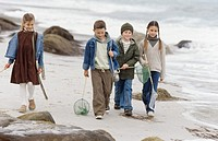 Four children walking on the beach