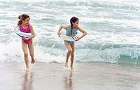 Two girls (8-9) playing at the beach