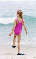 Girl (8-9) going into the sea with snorkel and fins