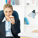 Front view portrait of businesswoman sitting at desk and holding cracker
