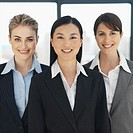 Front view portrait of three businesswomen smiling