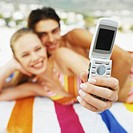 Front view portrait of young couple lying on beach taking picture with picture phone