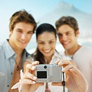 Front view portrait of three young people smiling and taking photograph