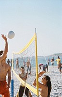Close-up of three young people playing volleyball on beach