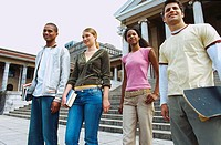 Low angle view of a group of young students standing on steps outside a building