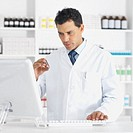 Close-up of pharmacist holding container of tablets