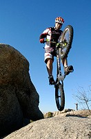 Man jumping from a rock doing bike trial