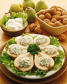 close-up of an appetizer of pear halves served on a bed of lettuce with sour cream and whole walnuts and pear beside it