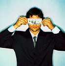 a businessman covering his eyes with a currency note