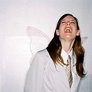 a business woman wearing angle wings and laughing