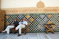 Tourists listening to audio guides while sitting in the shade at La Alhambra, Granada, Spain
