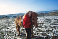 Young woman cuddling up to a horse with city and sea in background
