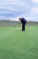 A golfer concentrating while putting