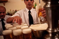 A man in black tie pouring beer