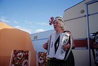 An elderly woman playing accordion