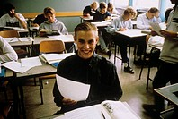 A smiling pupil holding a sheet of paper