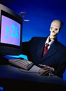 Human skeleton dressed as an business executive operating a computer