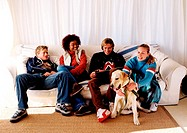 Two young couples sitting on a couch with a dog at their feet