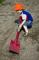 A boy digging a hole in gravel