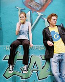 Teenage girl sitting on a ledge eating a candy bar with a teenage boy (15-17) standing beside her