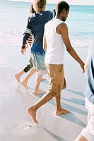 Group of young men walking on a beach