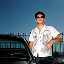 Portrait of a young man wearing sunglasses standing at the door of a car
