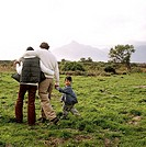 Rear view of a young couple walking in a meadow with their son (4-6)