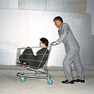 Elderly businessman pushing a shopping cart with a young businessman sitting inside