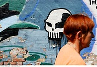 Woman passing graffiti wall with skull, Copenhagen, Denmark.