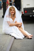 Bride sitting on curb smiling in the camera