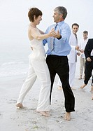 People in formalwear dancing on beach