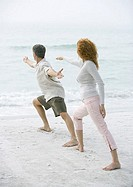 Mature couple doing tai chi on beach