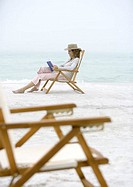 Woman on beach sitting in beach chair