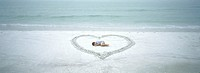 Child lying inside heart drawn on beach