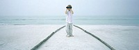 Boy looking through binoculars on beach