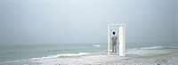 Man standing on beach, framed by doorframe