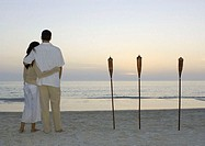 Couple standing on beach watching sunset