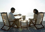 Newlyweds, husband serving wife champagne on beach