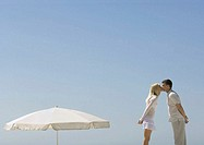Couple kissing next to parasol