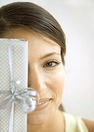 Woman holding gift in front of face