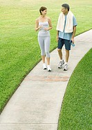 Mature couple walking on sidewalk in workout clothes