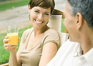 Woman holding glass of orange juice, looking at husband