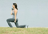 Woman working out by edge of water