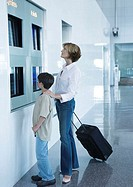 Mother and son looking at departure board in airport
