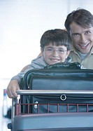 Man and son pushing luggage cart