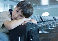 Boy resting head on suitcase in airport lounge